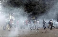 Opositores al presidente egipcio, Mohamed Mursi, chocaron con la policía el martes cuando miles de manifestantes presionaron aún más a los islamistas para que anulen un decreto que, según afirman, amenaza al país con una nueva era de autocracia. En la imagen, grupos de manifestantes corren por los gases lacrimógenos en la plaza Tahrir de El Cairo el 27 de noviembre de 2012. REUTERS/Asmaa Waguih
