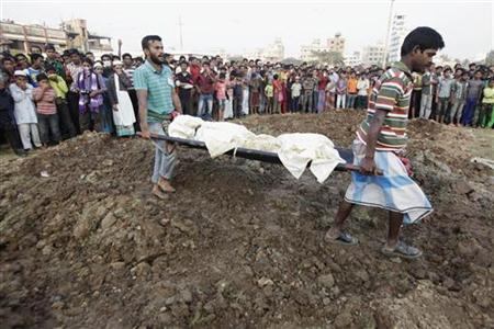 Workers carry a body of an unidentified garment worker, who died in a devastating fire in a garment factory, during a mass burial at a graveyard in Dhaka November 27, 2012. REUTERS/Andrew Biraj