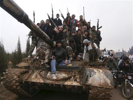 Free Syrian Army fighters pose on a tank, which they say was captured from the Syrian army loyal to President Bashar al-Assad, after clashes in Qasseer, near Homs November 19, 2012. REUTERS/Shaam News Network/Handout