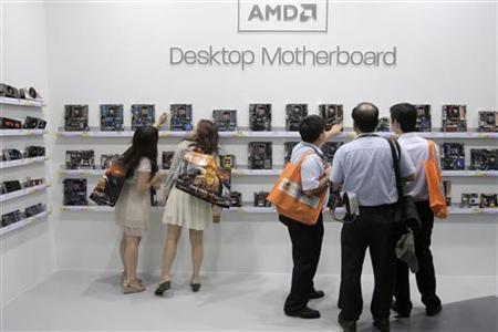 Visitors look at motherboards being displayed at the AMD booth during the 2012 Computex exhibition at the TWTC Nangang exhibition hall in Taipei June 6, 2012. REUTERS/Yi-ting Chung/Files