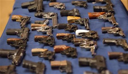 A view shows confiscated guns on a table during a news conference in New York October 12, 2012. REUTERS/Andrew Kelly