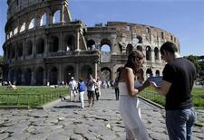 Tourists use an iPad tablet in front of Rome's ancient Colosseum September 20, 2012. REUTERS/Tony Gentile