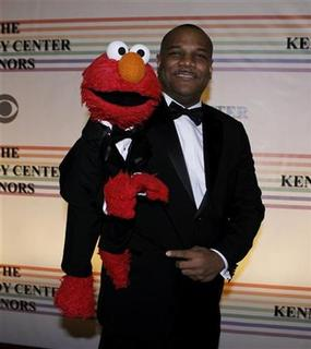 Sesame Street character Elmo and Kevin Clash pose for photographers on the red carpet at the Kennedy Center for the gala performance for the 2011 Kennedy Center Honors in Washington, December 4, 2011. REUTERS/Molly Riley