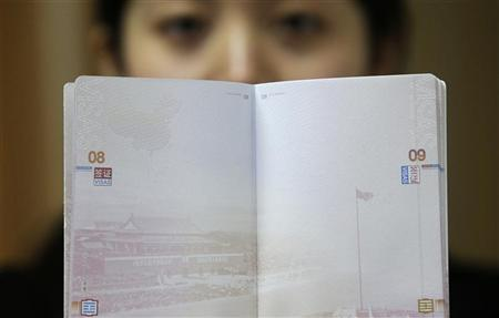 A woman holds a Chinese passport, displaying a Chinese map which includes an area in the South China Sea inside a line of dashes representing maritime territory claimed by China (L, top) and a picture of Beijing's Tiananmen Square (bottom), at an office in Wuhan airport, Hubei province, November 23, 2012. REUTERS/Stringer