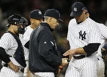 New York Yankees starting pitcher Andy Pettitte (R) is relieved by manager Joe Girardi as catcher Russell Martin (L) and third baseman Alex Rodriguez look on during the seventh inning of Game 1 of their MLB ALCS playoff baseball series in New York, October 13, 2012. REUTERS/Mike Segar
