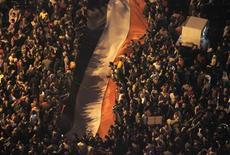 Decenas de miles de egipcios protestaron el martes contra el presidente Mohamed Mursi en una de las mayores manifestaciones desde la caída de Hosni Mubarak, acusando al líder islamista de buscar imponer una nueva autocracia. En la imagen, manifestantes contrarios al presidente de Egipto Mursi se concentran en torno a una bandera gigante del país mientras corean consignas contra el Ejecutivo islamista en la plaza Tahrir, en El Cairo, el 27 de noviembre de 2012. REUTERS/Asmaa Waguih