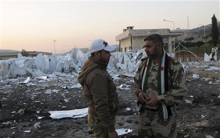 Free Syrian Army (FSA) fighters stand in front of an unfinished refugee camp that the FSA says was destroyed by Syrian regime air strikes in Bab Al-Hawa, near the Syria-Turkey border, November 26, 2012. REUTERS/Abdalghne Karoof