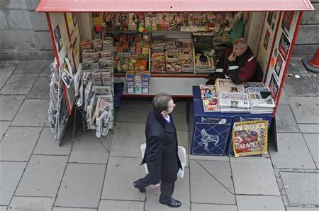 A man passes a newsagents stand displaying newspapers and magazines central London January 22, 2011. REUTERS/Luke MacGregor