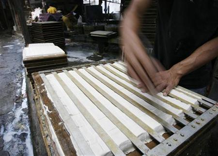 A worker cuts tofu before sending it to the market in a workshop in a home in Jakarta January 18, 2008. REUTERS/Enny Nuraheni/Files