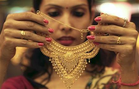 A salesgirl shows a gold necklace to customers at a jewellery showroom in the northern Indian city of Chandigarh November 11, 2012. REUTERS/Ajay Verma/Files