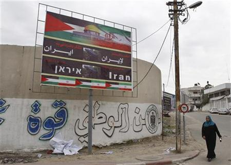 A Palestinian woman walks next to a banner that reads ''Thanks and gratitude to Iran'' in Gaza City November 27, 2012. REUTERS/Ahmed Zakot (GAZA - Tags: CIVIL UNREST CONFLICT)