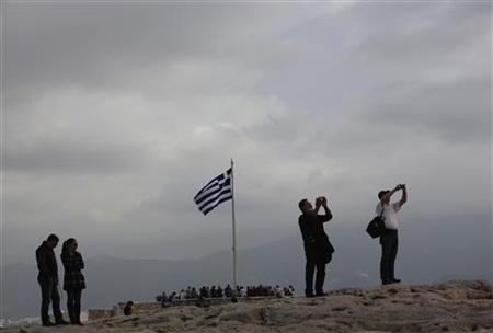 A Greek flag flutters at the Acropolis hill in Athens November 27, 2012. A bleary-eyed Greek Prime Minister Antonis Samaras welcomed on Tuesday an agreement by international lenders to help cut his country's debt and unblock bailout money to avert bankruptcy. REUTERS/John Kolesidis (GREECE - Tags: POLITICS BUSINESS TRAVEL)