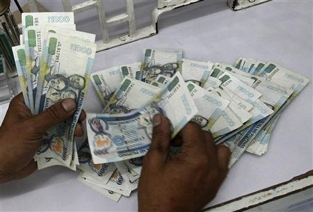 A worker counts one thousand pesos bills inside a money changer in Manila November 28, 2012. The Philippine peso hovered around its strongest level in more than 4-1/2 years on Wednesday after stronger growth data, while most other emerging Asian currencies slid on worries about the looming U.S. fiscal crisis and doubt on the Greece debt deal. REUTERS/Romeo Ranoco