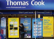 Женщина устанавливает рекламный плакат в отделении Thomas Cook в Лафборо (Англия), 14 декабря 2011 года. Старейшая в мире туристическая компания Thomas Cook отмечает хорошее начало зимнего сезона на своих основных рынках после нескольких тяжелых кварталов. REUTERS/Darren Staples
