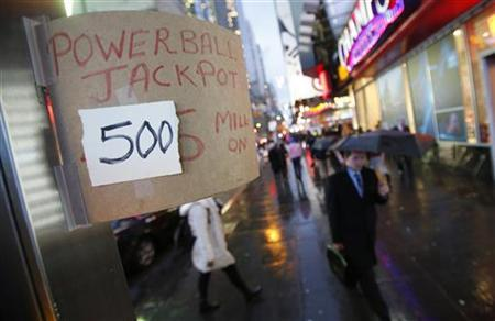 People with umbrellas walk past a sign advertising Powerball tickets at a newsstand in New York, November 27, 2012. REUTERS/Carlo Allegri