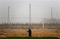 China alcanzará seguramente la meta del Gobierno de un crecimiento económico del 7,5 por ciento para el 2012 y podría incluso superarlo, dijo el miércoles el ministro de Comercio Chen Deming. En la imagen, un agricultor de cereales frente a las chimeneas de una fundición estatal en la ciudad de Tianying, en la provincia de Anhui, el 19 de noviembre de 2012. REUTERS/David Gray