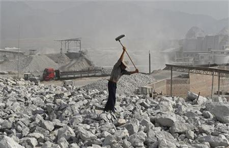 A worker smashes limestone inside a limestone mine in Quzhou, Zhejiang province October 12, 2012. REUTERS/Stringer