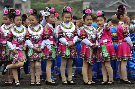 Ethnic Miao children wearing traditional costumes wait for a rehearsal of the celebration ceremony for the Miao's new year's day and the Guzang Festival in Leishan county, southeast Guizhou province, November 24, 2012. REUTERS/Sheng Li
