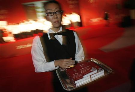 File photo of a woman dressed as a waitress carrying copies of ''Michelin Guide Tokyo 2008'' for members of the media during a party for the publication of the guide in Tokyo November 19, 2007. REUTERS/Kiyoshi Ota/Files.