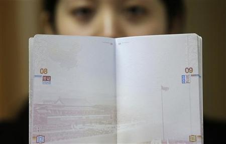 A woman holds a Chinese passport, displaying a Chinese map which includes an area in the South China Sea inside a line of dashes representing maritime territory claimed by China (L, top) and a picture of Beijing's Tiananmen Square (bottom), at an office in Wuhan airport, Hubei province, November 23, 2012. The Philippines and Vietnam condemned Chinese passports containing a map of China's disputed maritime claims on Thursday, branding the new design a violation of their sovereignty. REUTERS/Stringer