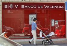 A man pushes a pram past a Banco de Valencia bank branch in Madrid June 25, 2012. REUTERS/Andrea Comas