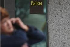 El grupo financiero nacionalizado BFA-Bankia espera volver a la senda de beneficios en 2013 tras registrar este año unas pérdidas récord de alrededor de 19.000 millones de euros, según un plan estratégico que contempla una amplia reducción de red y plantilla. En esta imagen de archivo, una mujer habla pr teléfono frente a una sucursal de Bankia en Madrid, el 26 de octubre de 2012. REUTERS/Sergio Pérez