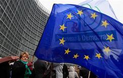 El Banco Central Europeo ha propuesto que el poderoso responsable de la competencia en la UE tenga un papel permanente para cerrar bancos débiles que sobreviven principalmente gracias a la financiación del banco central, según responsables familiarizados con la cuestión. En la imagen, una empleada de la UE en huelga sostiene una bandera de la institución frente a la sede de la Comisión Europea en Bruselas, el 21 de noviembre de 2012. REUTERS/Yves Herman