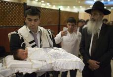 A Jewish man holds his baby son before his circumcision in Jerusalem in this September 24, 2012 file photograph. Circumcision is one of Judaism's most important laws and for generations of faithful it has symbolised a Biblical covenant with God. But in Israel, more and more Jewish parents are saying no to the blade. REUTERS/Ronen Zvulun/Files
