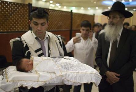 A Jewish man holds his baby son before his circumcision in Jerusalem in this September 24, 2012 file photograph. Circumcision is one of Judaism's most important laws and for generations of faithful it has symbolised a Biblical covenant with God. But in Israel, more and more Jewish parents are saying no to the blade. REUTERS-Ronen Zvulun-Files