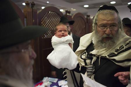 Rabbi Chaim Moshe Weisberg, a mohel or a Jewish ritual circumciser, holds a baby after circumcising him in Jerusalem in this September 24, 2012 file photo. REUTERS-Ronen Zvulun-Files