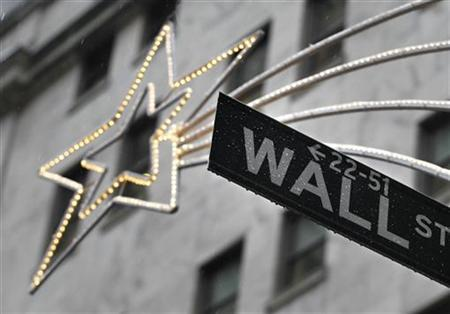 A holiday decoration is seen over Wall St. sign outside the New York Stock Exchange, November 27, 2012. REUTERS/Brendan McDermid