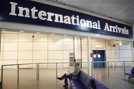 A man waits for arriving passengers in the international arrivals hall at Gatwick airport's north terminal, south of London November 30, 2011. REUTERS/Andrew Winning