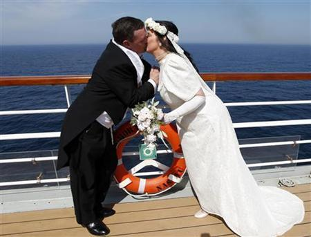 Derek (L) and Lynn Chambers of Belfast, ''Titanoracs'' who were married on Good Friday, kiss for photographers after a blessing on board the Titanic Memorial Cruise as it approached Halifax, Canada April 16, 2012. REUTERS/Chris Helgren (CANADA - Tags: ANNIVERSARY TRAVEL TPX IMAGES OF THE DAY)