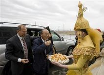 Президент Toshiba Corporation Atsutoshi Nishida пробует традиционные казахские изделия из теста, баурсаки, на церемонии открытия урановой шахты в южном Казахстане 24 апреля 2009 года. Казахстан может отменить мораторий на разработку недр. REUTERS/Shamil Zhumatov