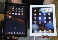 An employee holds up a Samsung Electronics' Galaxy Tab tablet computer (L) and an Apple iPad as he poses at a store in Seoul August 27, 2012. REUTERS/Lee Jae-Won
