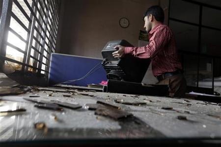 A staff member of a garment factory moves a damaged computer monitor after workers vandalised and set fire to the factory office during a protest against the death of their colleagues in a devastating fire, in Savar November 28, 2012. REUTERS/Andrew Biraj