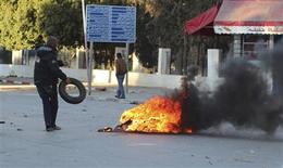 A protester burns tyres during clashes with police in Siliana November 28, 2012. At least 200 people were injured as Tunisians demanding jobs and economic development clashed with police on Wednesday, medical sources said, in the latest unrest to hit the country that spawned the Arab Spring uprisings. REUTERS/Mohamed Amine ben Aziza