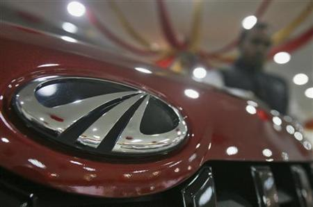 A customer stands next to a Mahindra vehicle on display inside the company's showroom in Chandigarh November 26, 2012. REUTERS/Ajay Verma