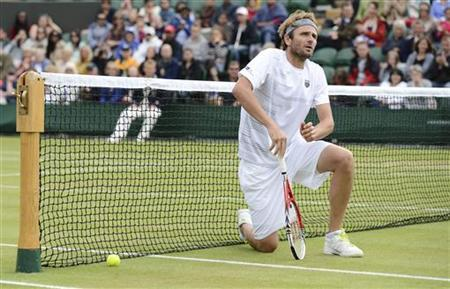 Mardy Fish of the U.S. reacts to missing a point during his men's singles tennis match against Jo-Wilfried Tsonga of France at the Wimbledon tennis championships in London July 3, 2012. REUTERS/Dylan Martinez/Files