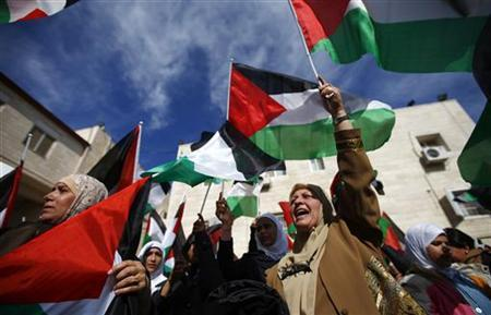 Palestinians wave flags during a rally in support of President Mahmoud Abbas' efforts to secure a diplomatic upgrade at the United Nations, in the West Bank city of Ramallah November 25, 2012. Abbas will visit New York this week as the Palestinians seek an upgrade of its observer status at the United Nations from that of an ''entity'' to a ''non-member state''. REUTERS/Marko Djurica