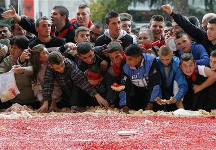 Children eat pieces of a giant cake, with the Albanian flag symbols and measuring 550 square metres (5920 square feet), prepared for the celebration of Albania's 100th Year of Independence in Tirana November 28, 2012. REUTERS/Arben Celi
