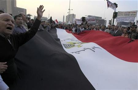 Anti-Mursi protesters chant anti-government slogans as they carry a large Egyptian flag at Tahrir Square in Cairo November 27, 2012. REUTERS/Mohamed Abd El Ghany