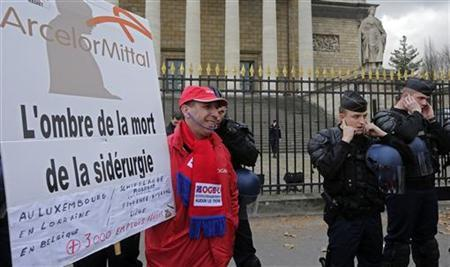 An Arcelor Mittal worker from Florange site stands next to French riot gendarmes and CRS riot police as they demonstrate in front the National Assembly in Paris November 28, 2012. REUTERS/Jacky Naegelen