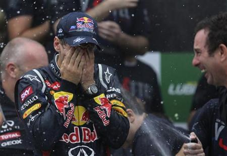 Red Bull Formula One driver Sebastian Vettel of Germany has champagne sprayed on him as he celebrates winning the world championship after the Brazilian F1 Grand Prix at Interlagos circuit in Sao Paulo November 25, 2012. REUTERS/Ricardo Moraes