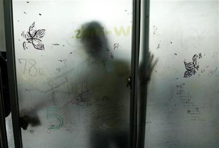 A student cleans the window in his high school classroom in Taipei on December 18, 2003. REUTERS/Simon Kwong/Files