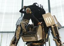 "Japanese artist Kogoro Kurata, inventor of the giant ""Kuratas"" robot, climbs out of its cockpit at an exhibition in Tokyo November 28, 2012. The four-meter-high, limited edition, made-to-order robot is controlled through a pilot in its cockpit, or via a smartphone. The four-tonne (4,000 kg) ""Kuratas"" can be customised in 16 different colours, and is armed with a futuristic weapons system, including a multi-rocket launcher that fires plastic rockets filled with compressed water. REUTERS/Kim Kyung-Hoon"