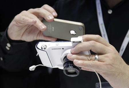 A man takes a picture of a Samsung Galaxy Camera during press preview day before the official start of the IFA consumer electronics fair in Berlin, in this August 30, 2012 file picture. South Korean consumer electronics giant Samsung Electronics Co is taking aim at its Japanese rivals with an Android-powered digital camera that allows users to swiftly and wirelessly upload pictures to social networking sites. REUTERS/Tobias Schwarz/File