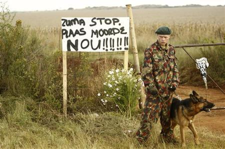 A guard stands next to a sign that reads, ''Zuma, stop farm murders now!'' before the funeral of white supremacist leader Eugene Terre'blanche outside his farm in Ventersdorp in South Africa's North West Province April 9, 2010. REUTERS/Siphiwe Sibeko