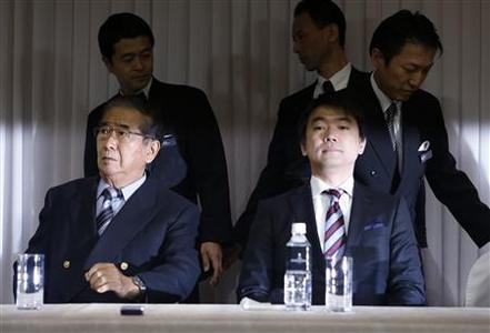 Japan Restoration Party leader and nationalist former Tokyo Governor Shintaro Ishihara (front L) and his deputy, Osaka Mayor Toru Hashimoto (front R) take their seats at a joint news conference to unveil their party's election campaign platform in Tokyo November 29, 2012. The new Japanese party that hopes to become a force to contend with in a Dec. 16 general election is calling for more defence spending to protect national interests and lower corporate and income taxes to bolster the economy, local media reported on Thursday. REUTERS/Issei Kato