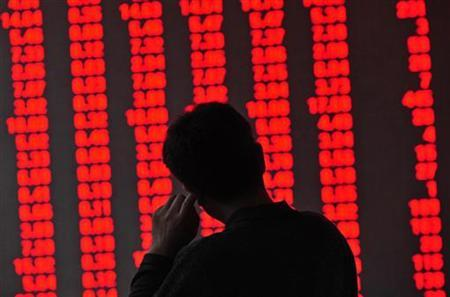 An investor looks at an electronic board showing stock information at a brokerage house in Shenyang, Liaoning province November 1, 2012. REUTERS/Stringer